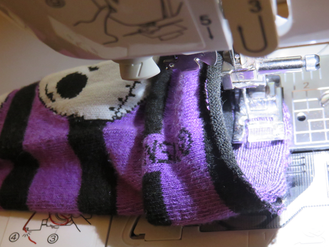 "Open up the sock so you can sew around the cuff to attach it.  Sew 1/2"" seam allowance all the way around.  Make sure not to sew the legging shut!"